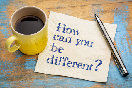 How can you be different? Handwriting on a napkin with a cup of espresso coffee