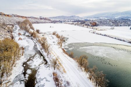 cache la poudre river: Poudre River, lake with water fowl  and Colorado foothills - aerial view of winter scenery