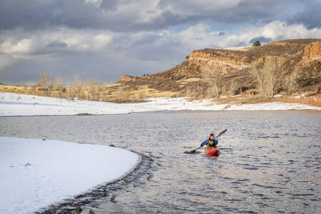 horsetooth reservoir: winter kayaking in Colorado - senior male paddler in a red whitewater kayak on  Horsetooth Reservoir near Fort Collins
