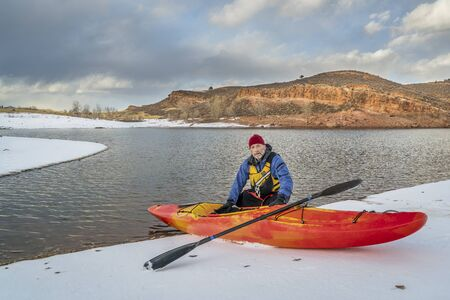 horsetooth reservoir: winter kayaking in Colorado - senior male with red whitewater kayak on shore of Horsetooth Reservoir near Fort Collins