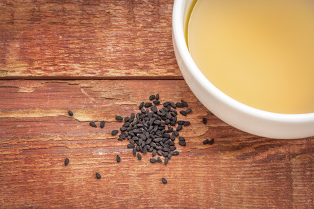 a seed: black cumin seeds (Nigella sativa) and oil in a small bowl against rustic bran wood