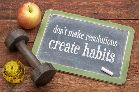 Do not make resolutions, create habits - advice on a vintage slate blackboard with a dumbbell Imagens
