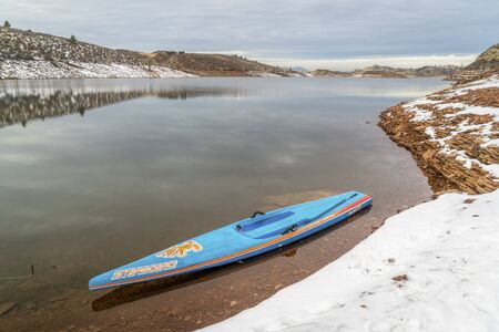 starboard: FORT COLLINS  CO, USA - DECEMBER 22, 2016: All Star racing stand up paddleboard by Starboard on a lake shore in winter scenery. Editorial