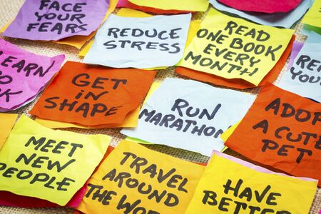 unrealistic: realistic and unrealistic  new year goals or resolutions - colorful sticky notes on canvas