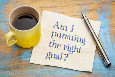 Am I pursuing the right goal question - handwriting on a napkin with a cup of espresso coffee