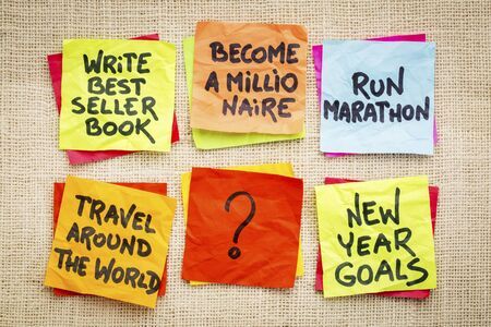 unrealistic: become a millionaire and other unrealistic new year goals or resolutions - colorful sticky notes on canvas