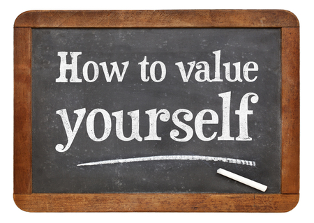 How to value yourself - white chalk text on a vintage slate blackboard Stock Photo