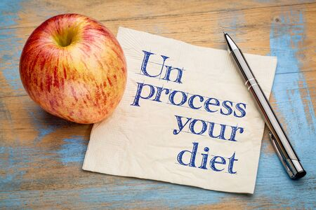 unprocessed: Unprocess your diet - healthy eating concept - handwriting on a napkin with apple