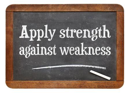 Aplicar la fuerza contra la debilidad - texto tiza blanca sobre una pizarra pizarra de la vendimia Foto de archivo - 68242794