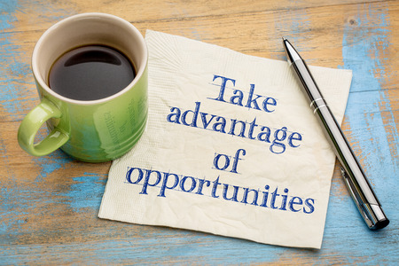 Take advantage of opportunities - handwriting on a napkin with a cup of espresso coffee
