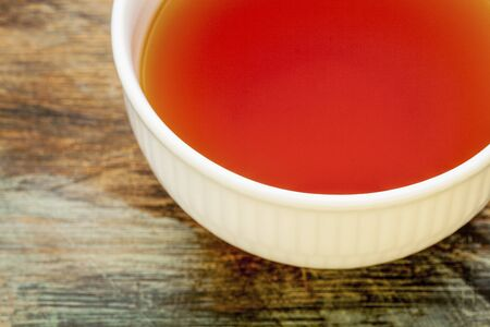 caffeine free: rooibos red tea made from the South African red bush, naturally caffeine free, white cup against grunge wood