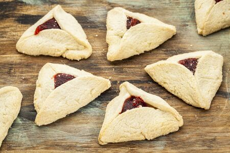 ashkenazi: raspberry  hamantaschen cookies  on a wooden cutting board - a traditional pastry in Ashkenazi Jewish cuisine for holiday of Purim
