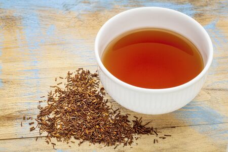 red bush tea: rooibos red tea  -  a white cup of a hot drink and loose leaves on grunge wood background, tea made from the South African red bush, naturally caffeine free Stock Photo