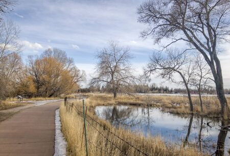 poudre river: recreational and commuting bike trail along the Poudre River in Fort Collins, Colorado, typical winter scenery with some snow