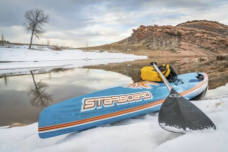 horsetooth reservoir: FORT COLLINS  CO, USA - JANUARY 1, 2017: Winter stand up paddling - All Star racing paddleboard by Starboard on a shore of Horsetooth Reservoir.