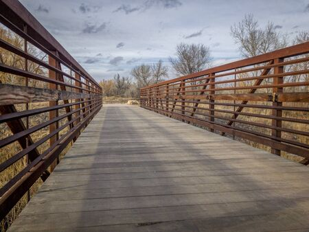 Footbridge on a recreational and commuting bike trail along the Poudre River in Fort Collins, Colorado, typical winter scenery