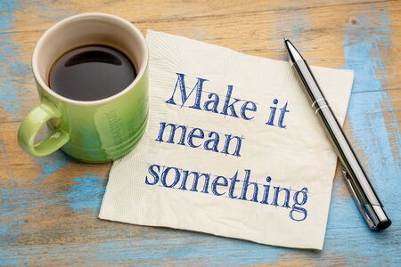 meaningful: Make it mean something - inspirational handwriting on a napkin with a cup of espresso coffee Stock Photo