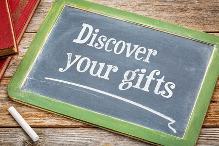 self discovery: Discover your gifts  - white chalk text on a slate blackboard with a stack of books against rustic wooden table