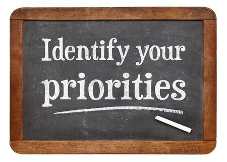 Identify your priorities - white chalk text on a vintage slate blackboard Фото со стока