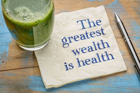 greatest: The greatest wealth is health advice or reminder - handwriting on a napkin with a glass of fresh, green, vegetable juice Stock Photo