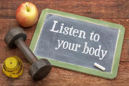 Escuche el concepto de su cuerpo: letrero de pizarra en pizarra contra madera de granero barnizada pintada de rojo con una mancuerna, manzana y cinta métrica. Foto de archivo