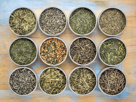 loose leaf: green tea sampler - top view of loose leaf teas in metal cans against grunge wood