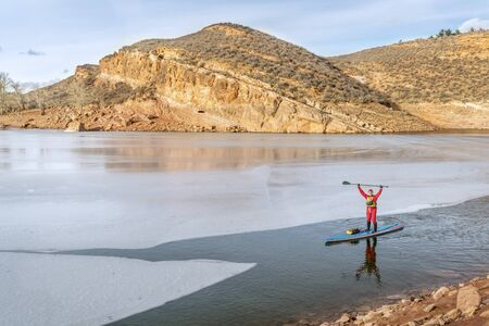 horsetooth reservoir: male paddler in drysuit  is enjoying stand up paddling on a partially frozen lake in Colorado - Horsetooth Reservoir near Fort Collins Stock Photo
