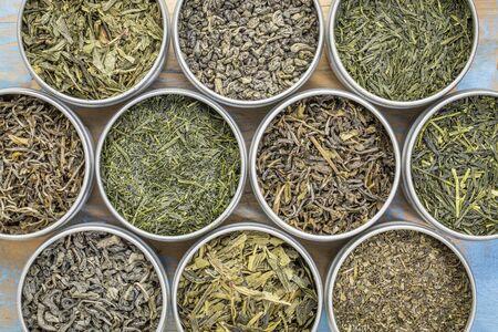gunpowder tea: green tea sampler - top view of loose leaf teas in metal cans against grunge wood