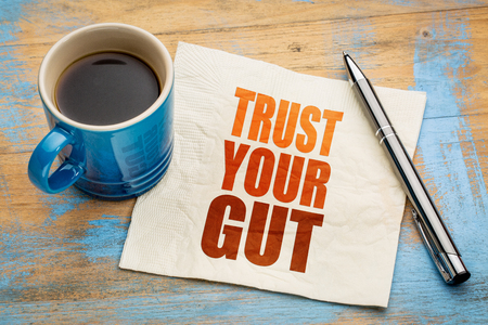 Trust your gut word abstract - advice or motivational reminder  on a napkin with cup of espresso coffee