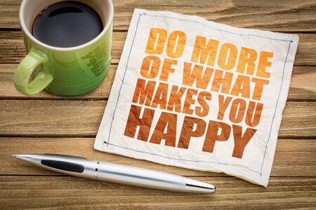 Haz más de lo que te hace feliz: resumen de palabras inspiradoras en una servilleta con una taza de café Foto de archivo - 68985030