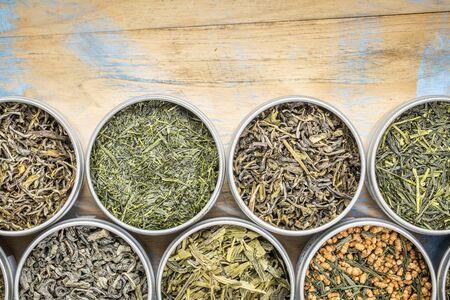 loose leaf: green tea sampler - top view of loose leaf teas in tins against grunge wood with a copy space