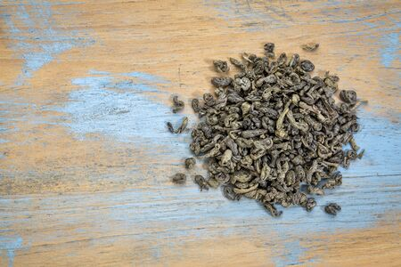 loose leaf: loose leaf Chinese gunpowder (pearl) green tea, a heap over grunge wood with a copy space, top view Stock Photo