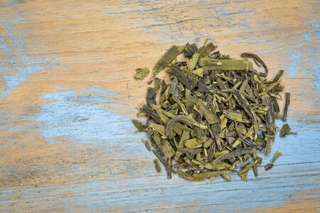loose leaf: Dragonwell (Longjing) loose leaf green tea, a heap over grunge wood with a copy space, top view