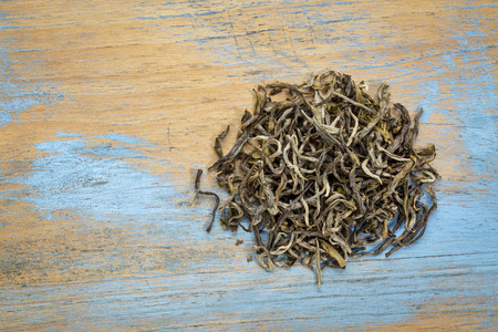 loose leaf: Yunnan Mao Feng  loose leaf  green tea, a heap over grunge wood with a copy space, top view