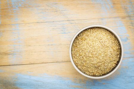 flaxseed: golden flaxseed meal - a ceramic bowl on grunge wood background with a copy space