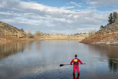 horsetooth reservoir: stand up paddler dressed in a drysuit  for cold season paddling on a shore of mountain lake in Colorado (Horsetooth Reservoir near Fort Collins)