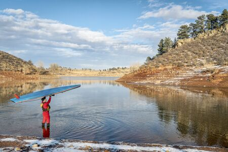 male paddler in drysuit is launching stand up paddleboard on a lake in Colorado, winter scenery Stock Photo