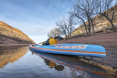 horsetooth reservoir: FORT COLLINS  CO, USA - JANUARY 22, 2017: Winter stand up paddling - All Star racing paddleboard by Starboard on a shore of Horsetooth Reservoir.