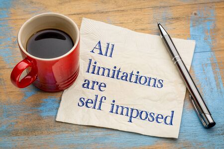 limitations: all limitations are self imposed - inspirational statement on a napkin with a cup of coffee