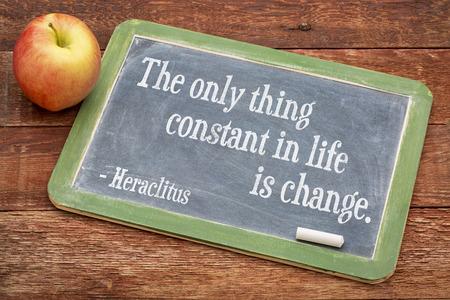 L'unica cosa costante nella vita è il cambiamento - citazione Heraclitus su una lavagna di ardesia contro il legno di grana rossa
