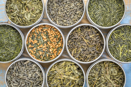 gunpowder tea: green tea sampler - top view of loose leaves  in metal cans against grunge wood Stock Photo