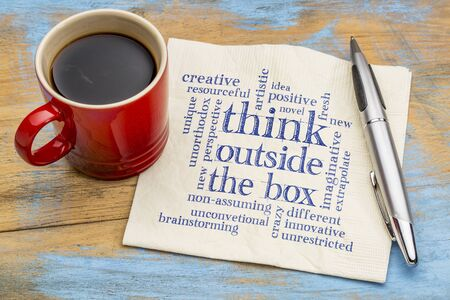 unorthodox: Think outside the box word cloud - handwriting on a napkin with a cup of coffee