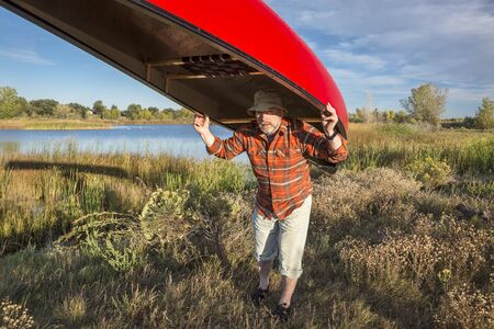 collins: senior male paddler is portaging a canoe between lakes, Riverbend Ponds Natural Area, Fort Collins, Colorado