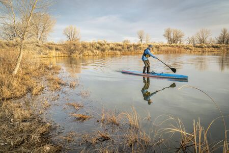 WInter or early spring training on a racing stand up paddling, a calm in Arapaho Bend Natural Area, Fort Collins, Colorado Stock Photo