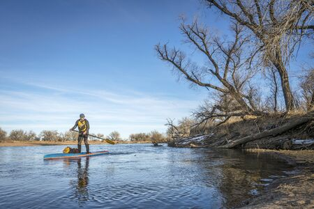 Expedition style winter stand up paddling on the South Platte RIver in eastern Colorado Stock Photo