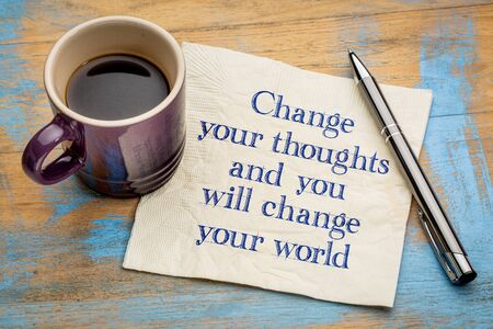 Change your thoughts and you will change your world - handwriting on a napkin with a cup of espresso coffee