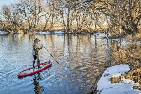 Stand up paddler poling on shallow river - Cache la Poudre River in Colorado winter scenery
