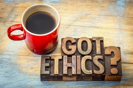 morale: Got ethics question - word abstract in vintage letterpress wood type with a cup of coffee