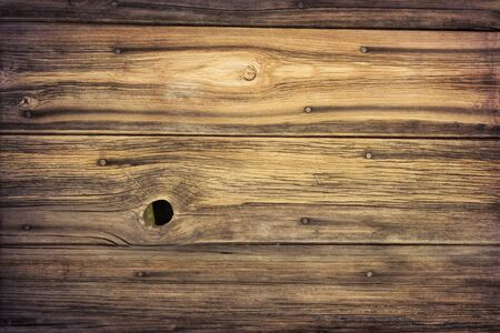 knothole: weathered grained wood of old barn wall with nails, staple and knothole