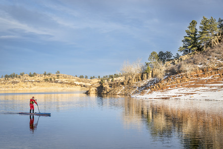 horsetooth reservoir: male paddler in a red drysuit  enjoying stand up paddling on a mountain lake in Colorado - Horsetooth Reservoir near Fort Collins Stock Photo